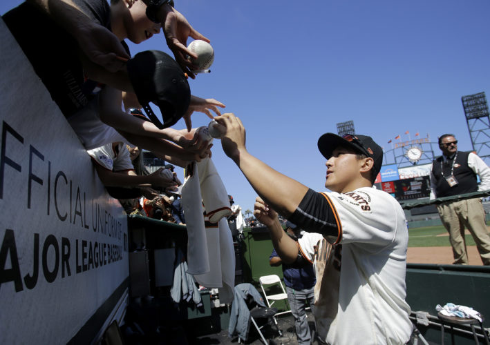 San Francisco Giants third baseman Jae-Gyun Hwang (1), of South Korea, signs autographs for fans after a baseball game against the Colorado Rockies in San Francisco, Wednesday, June 28, 2017. The Giants won 5-3. (AP Photo/Jeff Chiu)
