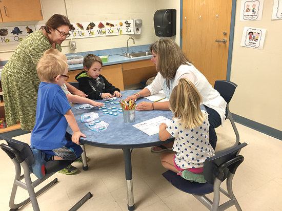 SETH NOLAN/Sun-Gazette Kindergarten teachers Anne Johnson, right, and Rae Pitchford, left, work with students involved in the summer readiness program.