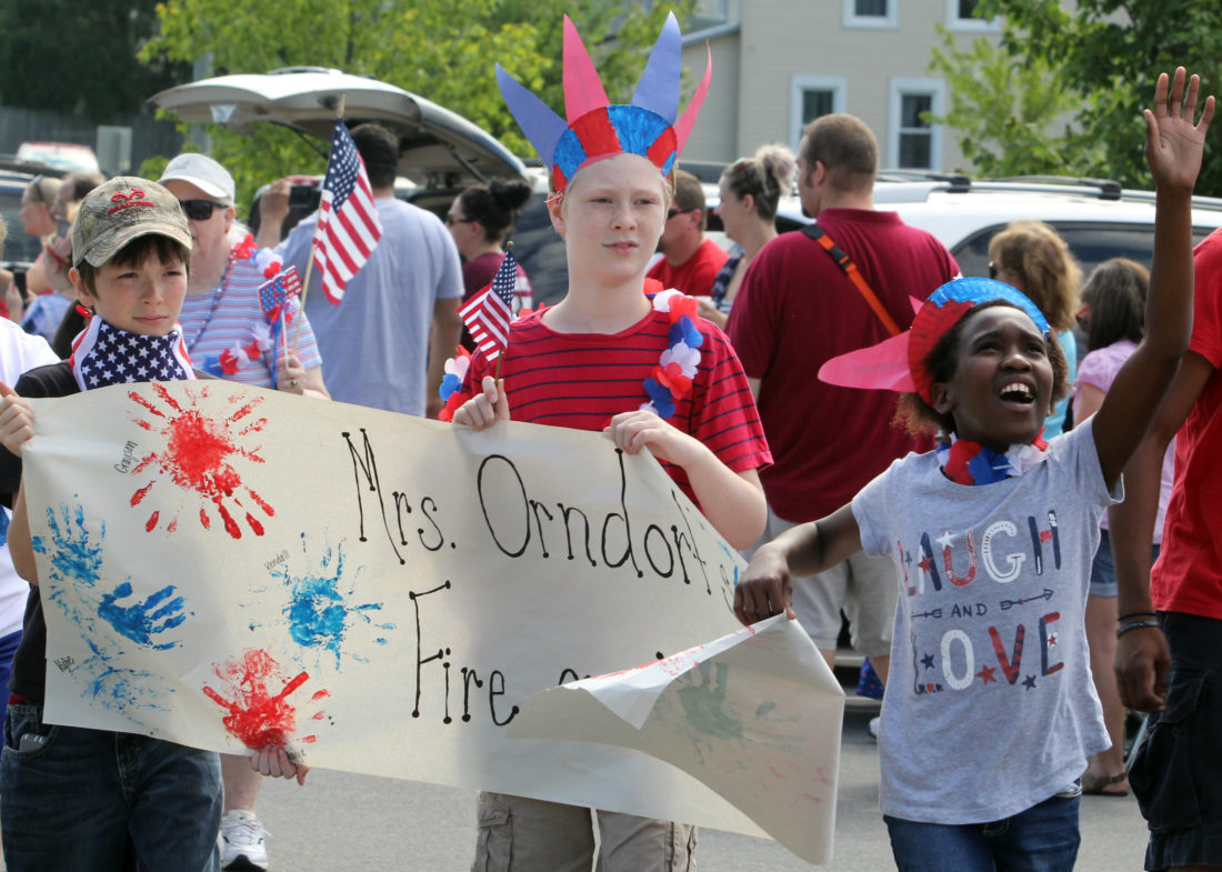 Students of Hayley Orndorf, Collin Dreese,  left; Grayson Smith, center; and Aniya Andreacci, right; march in the Extended School Year Fourth of July parade at Williamsport Area Middle School on Monday morning.