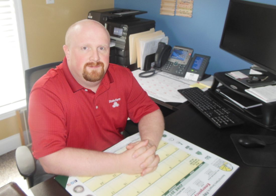 MIKE REUTHER/Sun-Gazette Jason Eberhart works at his desk at State Farm Insurance of Jersey Shore.