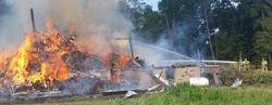 "PHILIP A. HOLMES/Sun-Gazette Jacob Heisey's barn was engulfed in flames when firefighters arrived on the scene Monday morning. Smoke billowed several hundred feet into the air. ""It looked like a bomb went off,"" one firefighter said, recalling his thoughts when he saw the smoke from a distance."