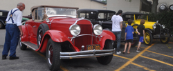 KEVIN CLARK/Sun-Gazette Correspondent Fans gather near a rare 1932 Chrysler Imperial Roadster, part of the vintage car tour of the Twin Tiers.