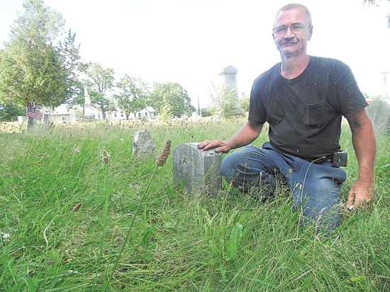 MIKE REUTHER/Sun-Gazette Larue Tressler kneels alongside a grave marker in the Williamsport Cemetery recently, showing how high the grass was before he and a group of volunteers mowed the grounds last weekend.