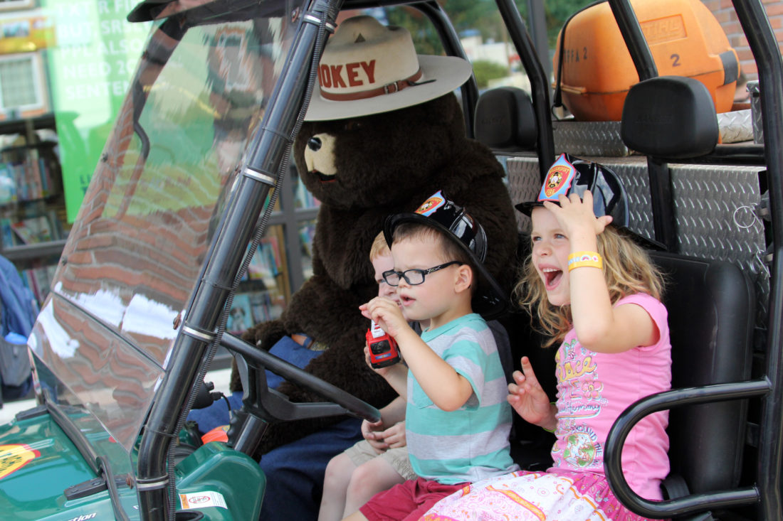 Harrison Weymer, 3, and his cousins Caleb Decker, 3, and Cadence Decker, 6,  from left to right, smile as they sit in a ATV with Smokey the Bear at the Touch-A-Truck event at the James V. Brown Library on Friday July 21, 2017. This is the third Touch-A-Truck event at the library. It was presented as part of the Build a Better World Summer Family Reading Programs. Tuesday July 25, 2017 the James V. Brown Library will hold a Bilingual Storytime with the Williamsport Crosscutters at 10:30am. KAREN VIBERT-KENNEDY/Sun-Gazette