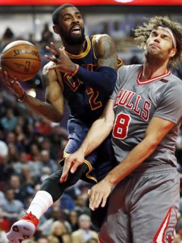 FILE - In this March 30, 2017, file photo, Cleveland Cavaliers guard Kyrie Irving, left, looks to pass against Chicago Bulls center Robin Lopez during the first half of an NBA basketball game, in Chicago. All-Star point guard Kyrie Irving recently asked to be traded. (AP Photo/Nam Y. Huh, File)