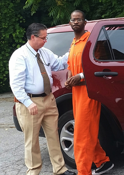 PHILIP A. HOLMES/Sun-Gazette Steven Curtis Reid, shown here with city police Lt. Brian Womer in June when he was arraigned on drug charges, was charged Tuesday for his alleged involvement in a city shooting on June 10.