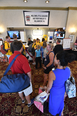 MARK NANCE/Sun-Gazette Little League fans from North Carolina wait to check in at the Genetti Hotel Wednesday afternoon.