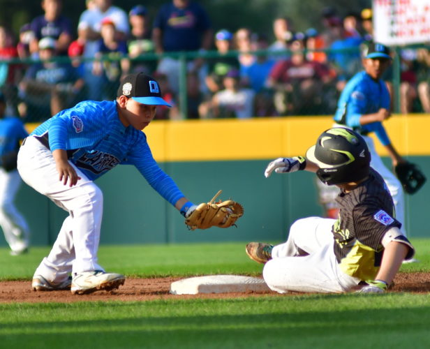 Dominican Republic second baseman Jeremy Solano is late on the tag on a double by Australia's Harrison Wheeldon in the first inning at Volunteer Stadium on Saturday evening.  (MARK NANCE/Sun-Gazette)