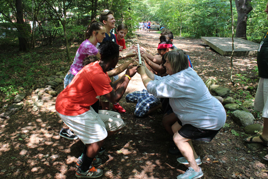 CARA MORNINGSTAR/Sun-Gazette Students try to put a pole on the ground all together in a group exercise during Williamsport Area High School Freshman Academy orientation day at Camp Susque recently.
