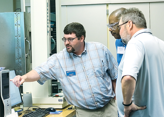 PHOTO PROVIDED Adam C. Barilla, instructor of plastics and polymer technology at Penn College, demonstrates tensile testing to participants during the 19th annual Extrusion Seminar & Hands-On Workshop at the college's Plastics Innovation and Resource Center.