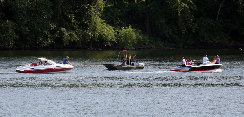 A boat is towed to safety after getting stuck near the dam on the Susquehanna River in Williamsport on Sunday afternoon. A city fire rescue boat , center, responded to the call for help, but a civilian stopped to tow the boat before the rescue boat arrived. KAREN VIBERT-KENNEDY/Sun-Gazette