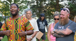 PAT CROSSLEY/Sun-Gazette Correspondent Eddie Kiersnowski, right, organizer of a rally for solidarity in Brandon Park on Sunday night, listens while Rasheed Wesley speaks to the group.