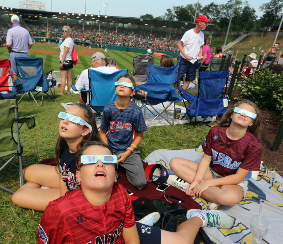 Brooke Granko, 13, brother Joey Granko, 11, and friends Dominickm Palma, 12, and Gia Lettieri, 13, from left to right, all from Old Forge, PA, take a look at the solar eclipse on Monday afternoon while at the Little League World Series.