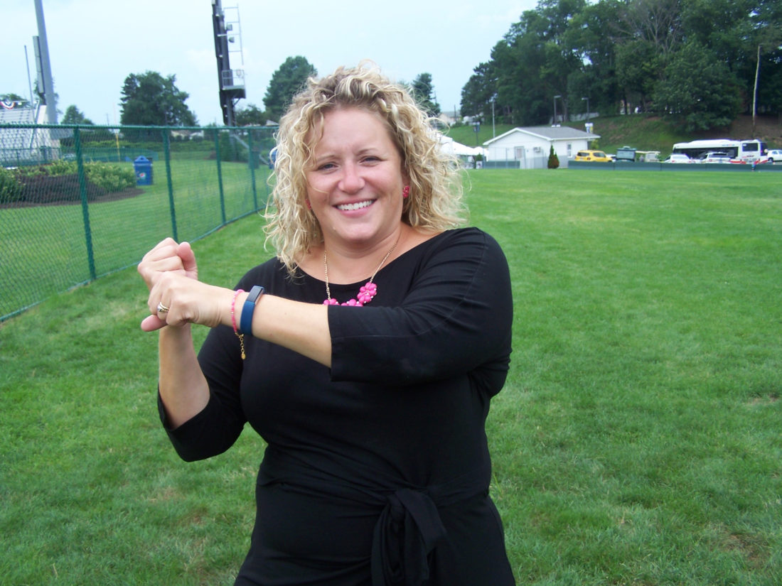 Sarah Moore demonstrates the American Sign Language sign for baseball behind Volunteer Stadium on Tuesday.
