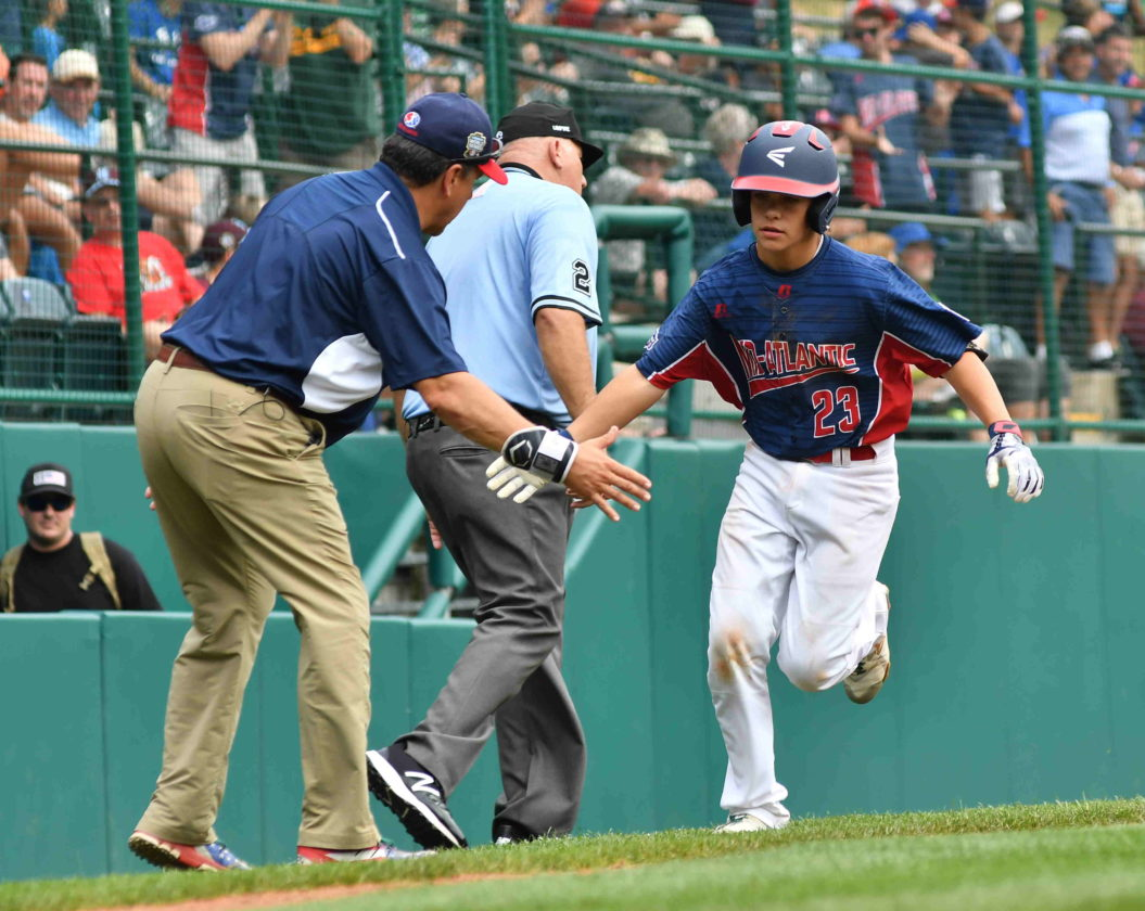 MARK NANCE/Sun-Gazette New Jersey's Chris Cartnick is congratulated by his third base coach after hitting a two-run home run in the sixth inning during a game against Connecticut on Thursday. (MARK NANCE/Sun-Gazette)