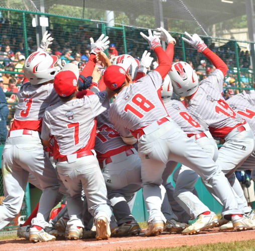 Japan teammates celebrate at home plate after Natsuki Yajima hit a home run in the third inning against Canada on Wednesday at Lamade Stadium. With the win, Japan advances to the International Championship on Saturday and awaits the winner of today's Mexico and Canada game. (MARK NANCE/Sun-Gazette)