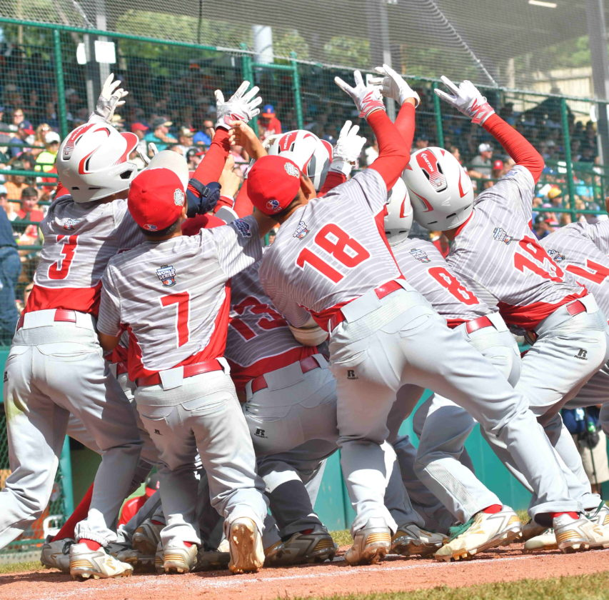 Japan teammates celebrate at home plate after Natsuki Yajima hit a home run in the third inning against Canada on Wednesday at Lamade Stadium. With the win, Japan advances to the International Championship on Saturday and awaits the winner of today's Mexico andCanada game. (MARK NANCE/Sun-Gazette)