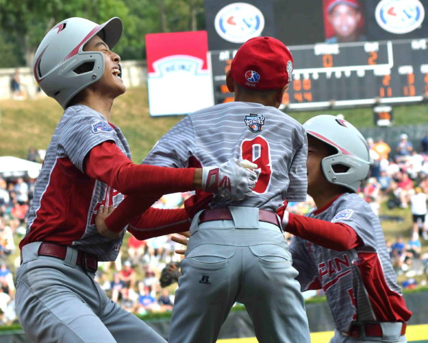 Members of the Japanese team celebrate with one another after winning the Little League World Series by defeating Texas, 12-2, in five innings on Sunday at Lamade Stadium.  (MARK NANCE/Sun-Gazette)