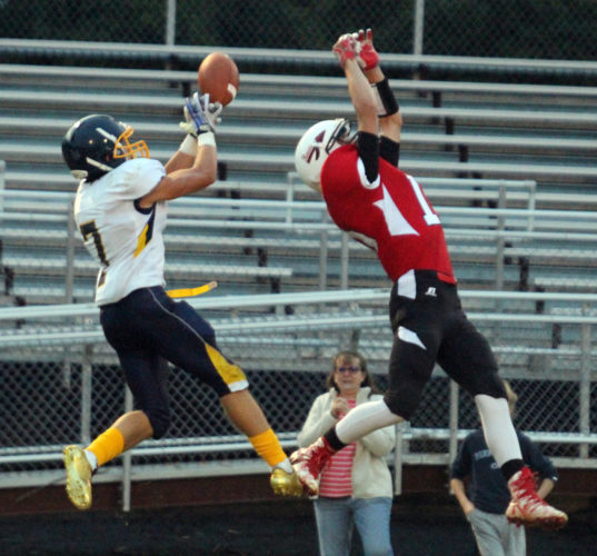 KAREN VIBERT-KENNEDY/Sun-Gazette Montgomery's Steven Prince, right, reaches for a pass intended for Cowanesque Valley's Matt Barber Friday night, in a game Montgomery won to even its record at 1-1.