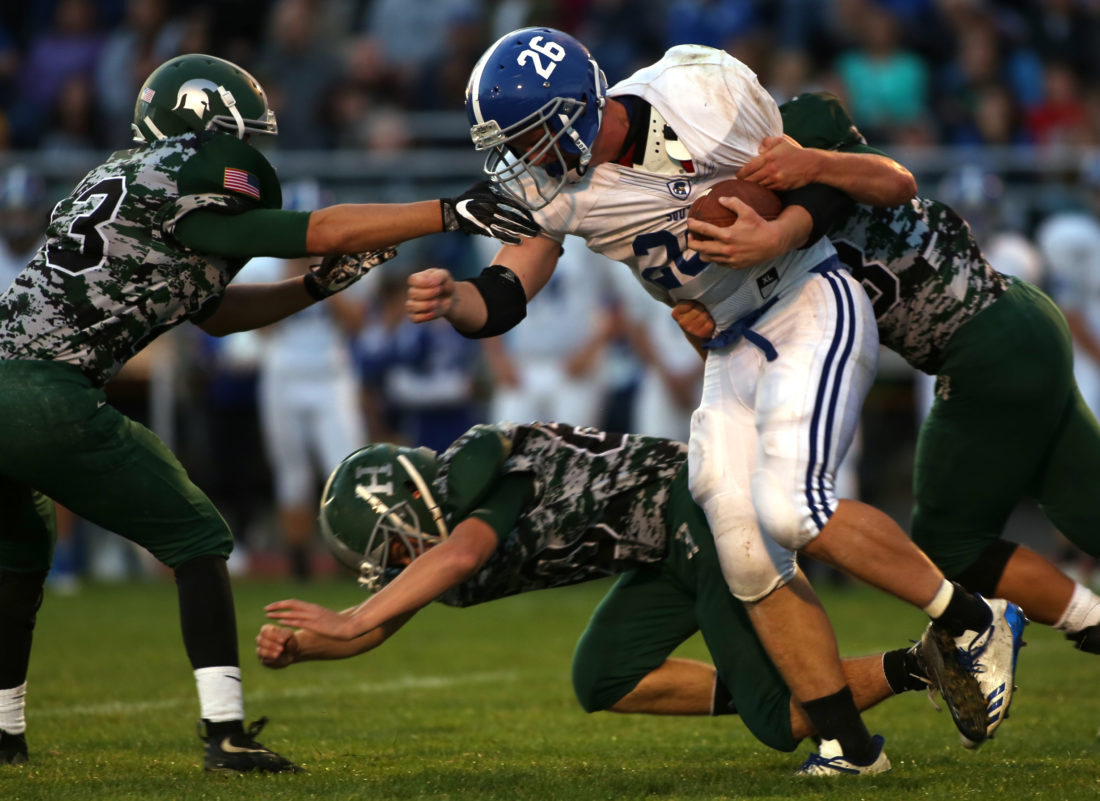 DAVE KENNEDY/Sun-Gazette Corresponden Gideon Green (26) of South Williamsport is brought down by several Hughesville players Friday night at Hughesville.