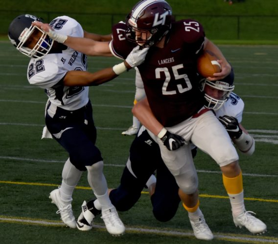 JUDI PINKERTON/For The Sun-Gazette Cole Cavanaugh of Loyalsock stiff-arms Chris Day of Mifflinburg before being tackled by Garrett Becker Friday night.