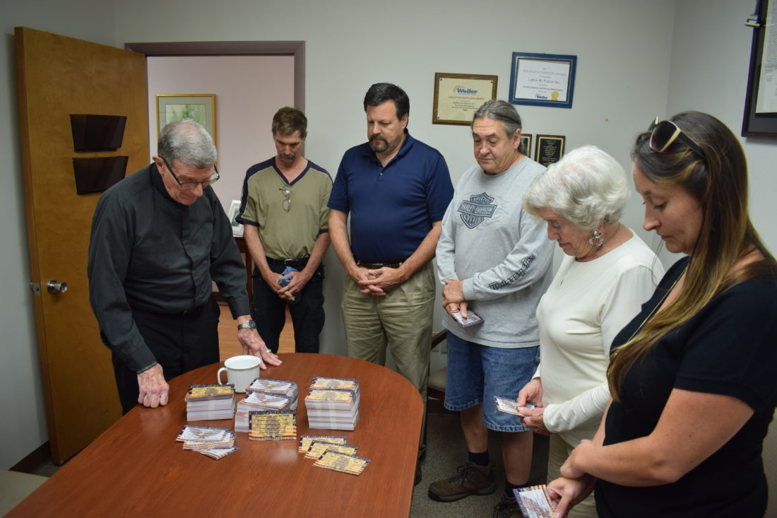 "IOANNIS PASHAKIS/ Sun-Gazette Father John Manno, at left, blesses the Fallen Warrior cards that will be handed out to riders before the annual 9-11 Memorial Ride. The cards carry 6,860 names of soldiers who died in Afghanistan and Iraq since Sept. 11, 2001. From left of Manno are Mark Porten, Joe Pulizzi, Thomas ""Tank"" Baird, Charlene Pulizzi and Nisha Brelsford."