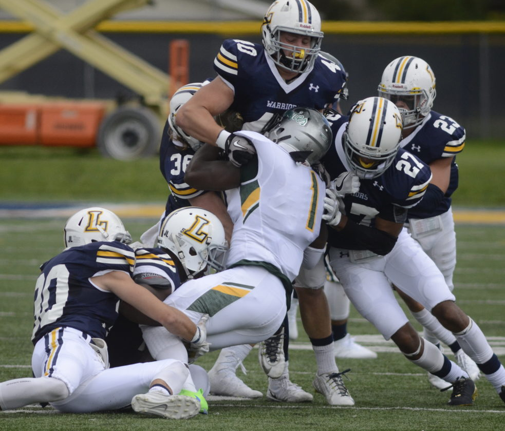 A handful of Lycoming College defenders pull down Delaware Valley's Devauntay Ellis during a MAC game on Saturday at David Person Field in Williamsport. (RALPH WILSON/For The Sun-Gazette)