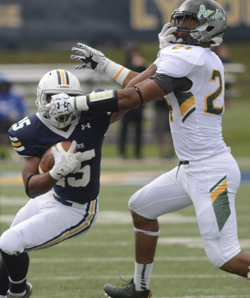 RALPH WILSON/Sun-Gazette Correspondent Lycoming College's Dante Gipson (25) pushes past Delaware Valley's   Michael Ockimey (24) during a MAC college football game on Saturday at David Person Field in Williamsport. Delaware Valley won 34-3.