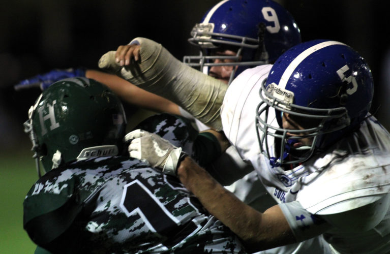 DAVE KENNEDY/Sun-Gazette Correspondenta Luke Winner (9) and Chris Klem (5) of South Williamsport bring down Ori Shaner (12) of Hughesville in the first half Friday at Hughesville as South improved to 2-1.