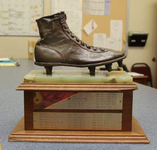 "KAREN VIBERT-KENNEDY/Sun-Gazette The inscription on the back of the Old Shoe trophy reads, ""The Old Shoe trophy or shoe of the unknown football player"" was born in 1961 when, during a discussion concerning an appropriate award for the winner of the annual Muncy/Montgomery football game, Dick Dietz and George Sauers picked a shoe out of a pile of leftovers in the Muncy gym and thus a tradition was born. The Muncy Jaycees had it bronzed and placed on the trophy to be given to the school that won the rival football game each year."