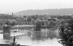 """SUN-GAZETTE FILE PHOTO The first two spans of the 97-year-old iron-truss bridge over the Susquehanna River at Maynard Street are brought down in this photo that was published on June 7, 1986. The iron-truss bridge was not the original at the site but had been built to replace a wooden structure after the Great Flood of 1889. The iron version was described by its builders in 1889 as the """"most perfect and lasting (bridge design) available."""" The original bridge on Maynard Street was built by lumber baron Peter Herdic to serve people to whom he sold lots on the other side of the river."""