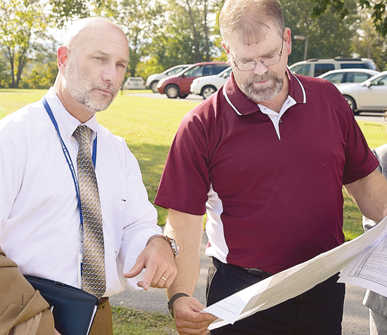 IOANNIS PASHAKIS/Sun-Gazette  Britt Bassett, right, president of Bassett Engineering, shows Rick Vilello, deputy secretary of the state Department of Community and Economic Development, the plans for the park outside of Nippenose Valley Village.