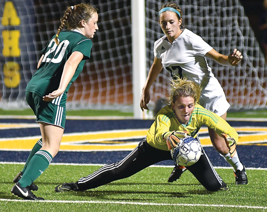 MARK NANCE/Sun-Gazette Lewisburg goal keepr Bethany Rippon dives for the lose ball as team mate Chloe Michaels (2) helps defend on an attempted head shot by Montoursville's Erin Witter (27) in the second half.