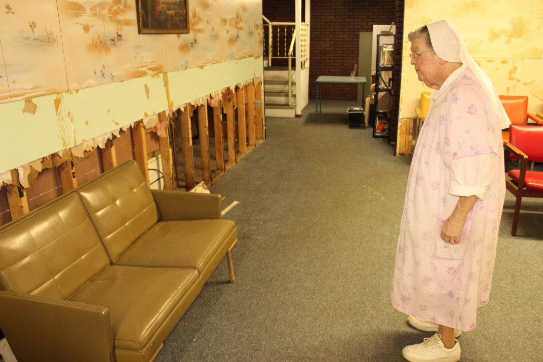 CARA MORNINGSTAR/Sun-Gazette Sister Henry Lambert, of Sisters of Charity, looks at the remains of the waiting room area inside St. Anthony's Center, 125 E. Willow St. Flood damage inside the St. Anthony's Center caused the free clinic area to shut down. The soup kitchen remains open, but the clinic has no current plans to reopen.