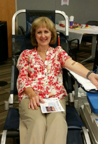 Beth Russell donates blood during a recent inaugural blood drive born of a partnership between the health organization and Community Blood Bank.