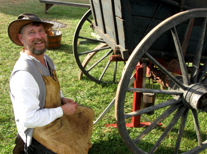 D. EVERETT SMITH/Sun-Gazette Correspondent As a reenactor, Bradd Mertz, of Pottsgrove, above, portrays a wheelwright. A wheelwright removes and repairs the wheels of a wagon. He said he got into this years ago when a history teacher suggested he get involved. Warm, dry weather greeted visitors to the Fort Freeland Heritage Days Festival Saturday and Sunday at Warrior Run Middle and High School in Turbotville, but rainy days likely are ahead.