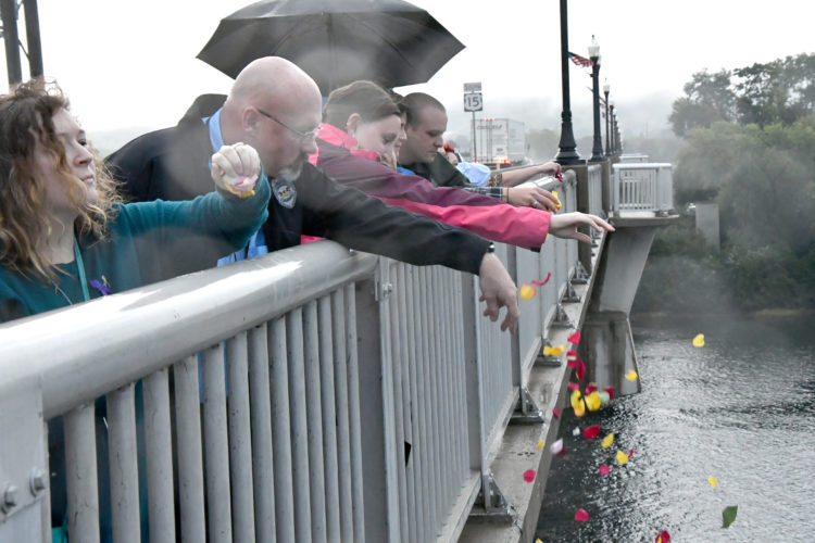 MARK NANCE/Sun-Gazette Walkers toss rose petals into the Susquehanna River from the Carl E. Stotz Little League Memorial Bridge in memory of those lost to domestic violence during the Walk of Remembrance Wednesday. The walk to the bridge was part of the YWCA's Domestic Violence Vigil at the Commissioners Boardroom.