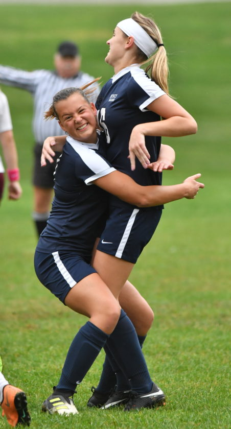 Muncy's Bailey Bowen, left, hugs Alivia Heivly after Heivly's goal with 6:49 left in the first half. Muncy won, 8-0, in the Mid-Penn Conference game. (MARK NANCE/Sun-Gazette)