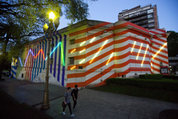 This Monday, Oct. 9, 2017 photo shows the usually impeccably white Palais de Glace in bright-colored stripes and wrapped in neon lights painted by French artist Bertrand Ivanoff as part of the recent opening of the South American biennale, Bienalsur in Buenos Aires, Argentina. Established biennales like Venice are run by one curator who chooses a common theme. At Bienalsur, though, the themes are wide ranging - from humankindÕs relation with nature to borders and immigration. (AP Photo/Victor R. Caivano)