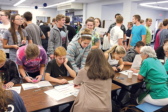 CARA MORNINGSTAR/Sun-Gazette Students gather together at the end of their budget experience to total up costs and see if they have any money left over with the help of financial advisors during the Financial Reality Fair at the Muncy Junior-Senior High School.