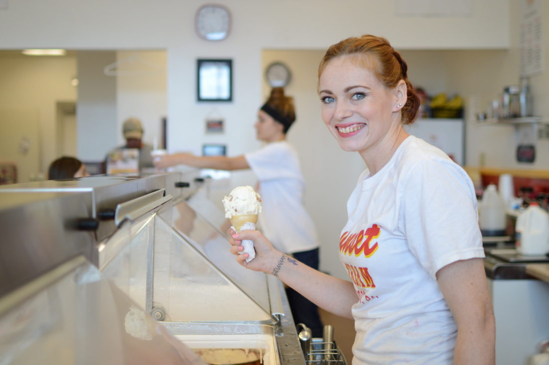 """Jessica McDermott scoops ice cream into a cone at her store, with the purple ribbon and """"Survivor"""" tattoo visible on her wrist."""
