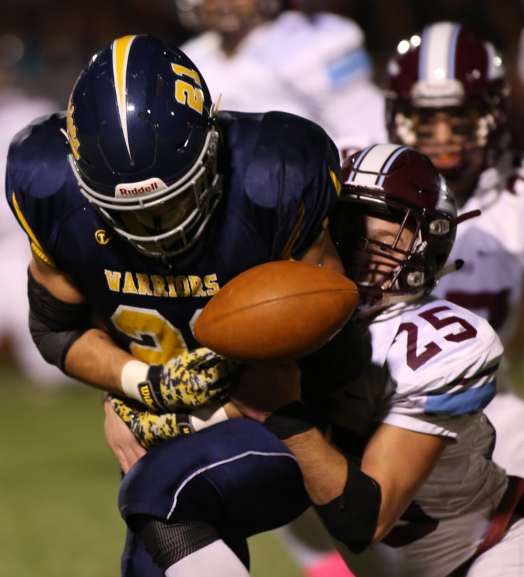 DAVE KENNEDY/Sun-Gazette Correspondent Oleg Bohner (21) of Montoursville runs with the ball as Cole Cavanaugh (25) of Loyalsock reaches in and strips it Friday at Montoursville.