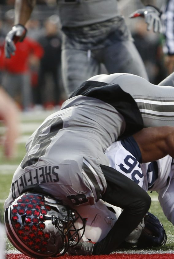 ASSOCIATED PRESS Ohio State cornerback Kendall Sheffield, top, tackles Penn State running back Saquon Barkley for a loss during the second half Saturday in Columbus, Ohio.