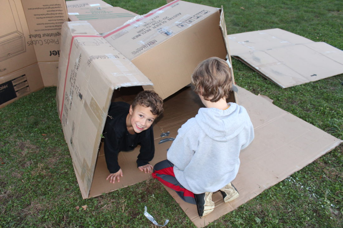 CARA MORNINGSTAR/Sun-Gazette Cooper Mackey, 6, and his brother Jackson Mackey, 10, work on getting their cardboard box camp for the evening set up during the Box City event for Family Promise of Lycoming County and American Rescue Workers at Lycoming College campus on Friday. Participants slept in cardboard boxes overnight in order to promote awareness for homelessness.