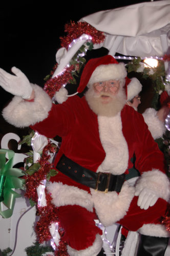RASHELLE CAREY/Sun-Gazette Santa waves to the crowd at Williamsport's Holiday Parade Friday night as he makes his way down Fourth Street to the new Santa house at the corner of Fourth and Hepburn. Here Brenden Kuriga, 3, son of Chris and Erin Kuriga, as well as other 3 to 9-year-olds played bells with the Annabells of St. John's Newberry United Methodist Church after the lighting of the downtown Christmas Tree.