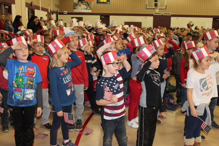 CARA MORNINGSTAR/Sun-Gazette Elementary students sing songs and salute the veterans in thanks during the Veteran's Day activities at Lyter Elementary School in Montoursville on Monday.