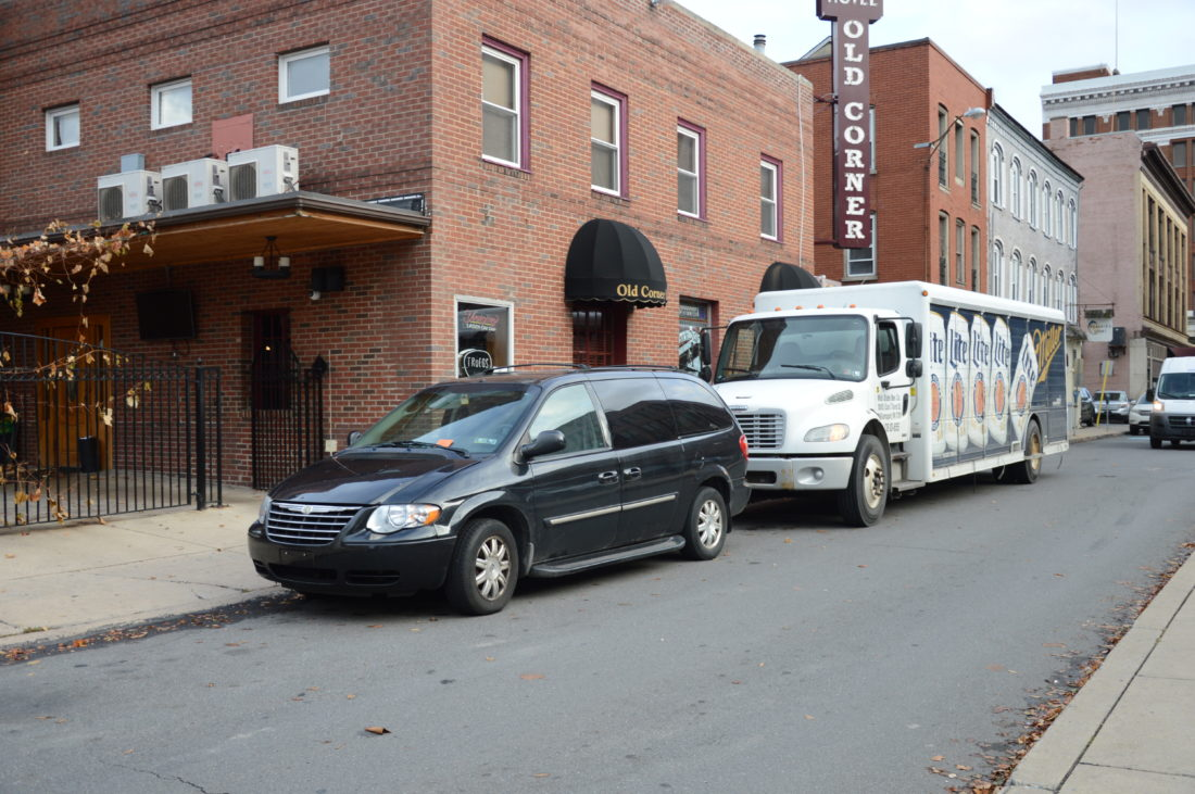 KATELYN HIBBARD/Sun-Gazette A van with a parking ticket on the window sits in a no-parking zone in front of the Old Corner restaurant on Court Street with a Miller Lite delivery truck parked behind it.