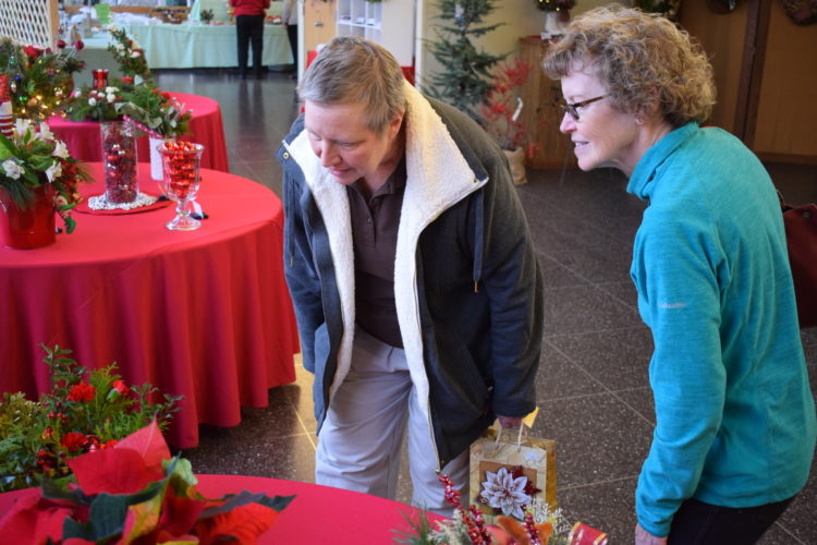 Suzan Weaver, left, and Kathy Gingerich, right, look through the many festive decorations at the Holiday House hosted by the DuBoistown Garden Club at The Lycoming College Academic Center.