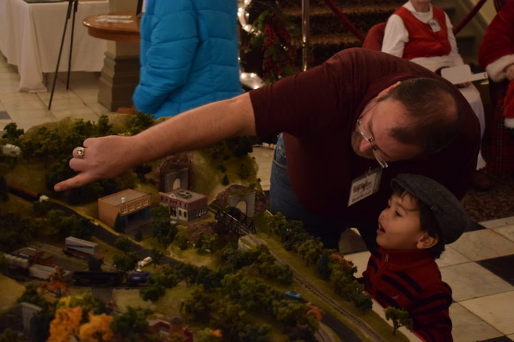 IOANNIS PASHAKIS/ Sun-Gazette Brett Hinkal of the Will Huffman Toy Train Expo, shows little Gideon Garza, 2, how the trains work on a model.