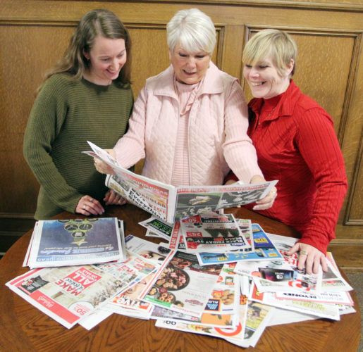 Beth Miller, left, Linda Neupauer, center, and Cheryl Johnson, right, of the Williamsport Sun-Gazette classified department look over the Thanksgiving day sale flyers. KAREN VIBERT-KENNEDY/Sun-Gazette
